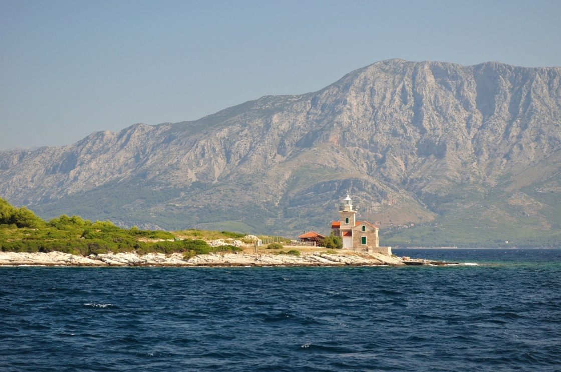 Lighthouse on south end of island Hvar in Adriatic sea with mountain Biokovo in background. Sucuraj, Croatia
